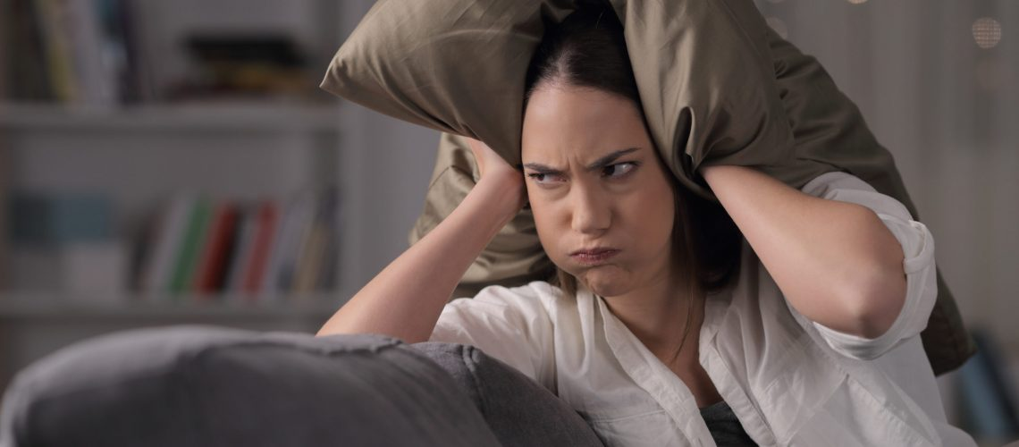 Angry homeowner suffering neighbor noise covering ears